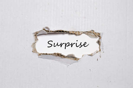 provoke: The word surprise appearing behind torn paper