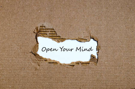 differently: The word open your mind appearing behind torn paper