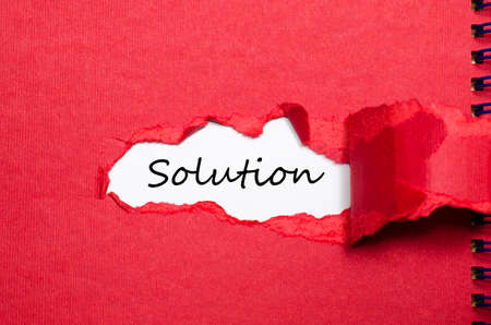 appearing: The word solution appearing behind torn paper Stock Photo