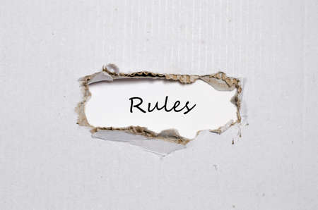 appearing: The word rules appearing behind torn paper