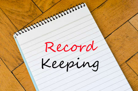 data protection act: Record keeping text on White notepad on the wooden background
