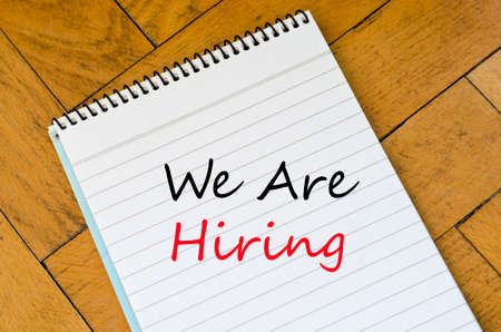 recruit help: We are hiring text on White notepad on the wooden background Stock Photo