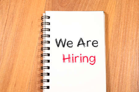 recruit help: We are hiring news text concept write on notebook