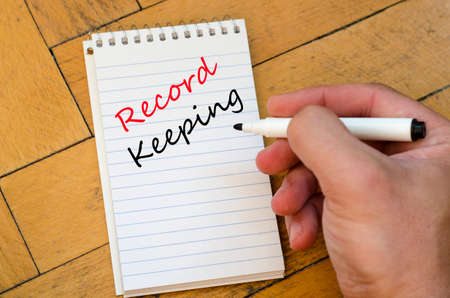 data protection act: Record keeping text on White notepad and human hand on the wooden background Stock Photo