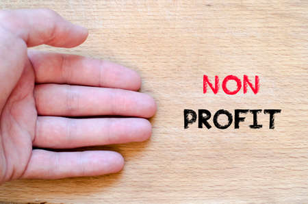 non profit: Human hand over wooden background and non profit text concept