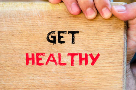 longevity medicine: Human hand over wooden background and get healthy text concept