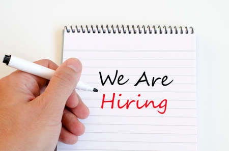 recruit help: We are hiring on White notepad and human hand on the wooden background Stock Photo