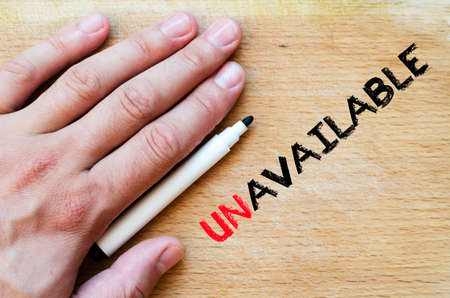 unavailable: Human hand over wooden background and unavailable text concept Stock Photo
