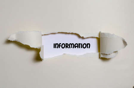 appearing: The word information appearing behind torn paper Stock Photo