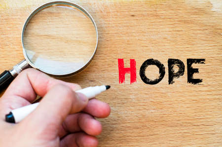 Human hand over wooden background and hope text concept Stock Photo