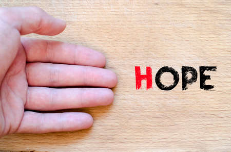 braveness: Human hand over wooden background and hope text concept Stock Photo