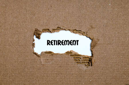 appearing: The word retirement appearing behind torn paper Stock Photo