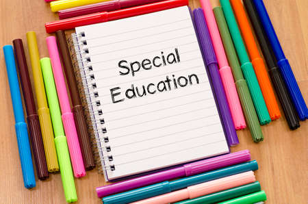 special education: Felt-tip pen and notepad on a wooden background and special education text concept Stock Photo