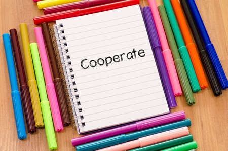 cooperate: Felt-tip pen and notepad on a wooden background and cooperate text concept