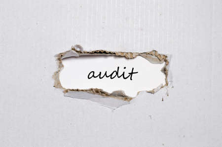 appearing: The word audit appearing behind torn paper