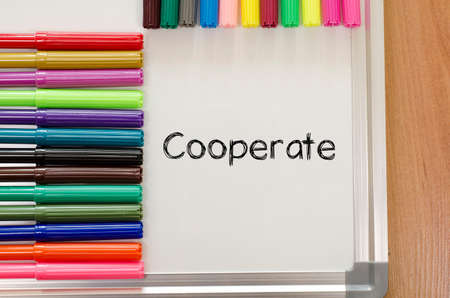 cooperate: Felt-tip pen and whiteboard on a wooden background and cooperate text concept