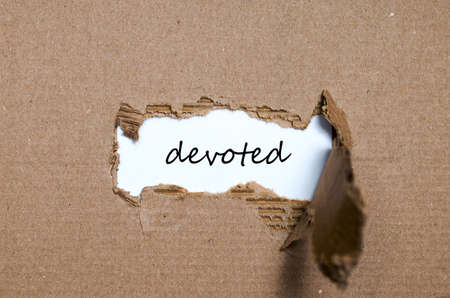 transcription: The word devoted appearing behind torn paper Stock Photo