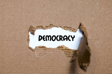 The word democracy appearing behind torn paper