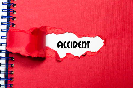 appearing: The word accident appearing behind torn paper