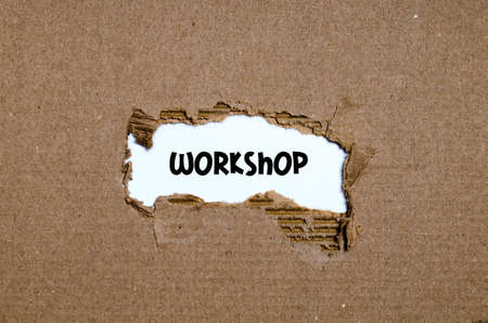 appearing: The word workshop appearing behind torn paper Stock Photo