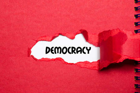 appearing: The word democracy appearing behind torn paper