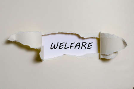 payer: The word welfare appearing behind torn paper