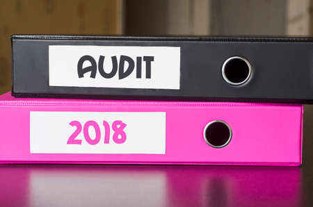 conformance: Bright office folders over dark background and audit 2018 text concept