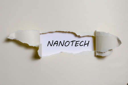 appearing: The word nanotech appearing behind torn paper Stock Photo