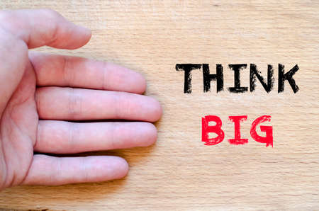 contracting: Human hand over wooden background and think big text concept Stock Photo