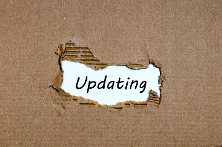 appearing: The word updating appearing behind torn paper Stock Photo