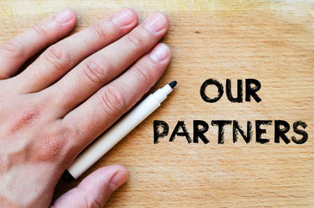 our: Human hand over wooden background and our partners text concept