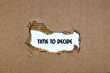 decide: The word time to decide appearing behind torn paper Stock Photo