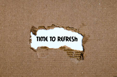 tearing down: The word time to refresh appearing behind torn paper