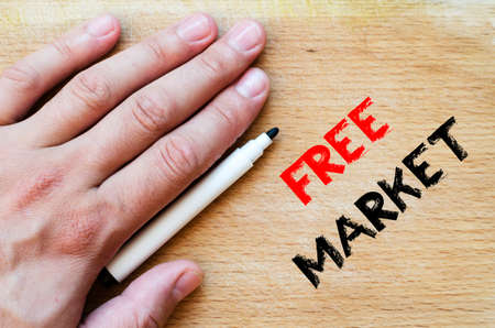 free enterprise: Human hand over wooden background and free market text concept Stock Photo