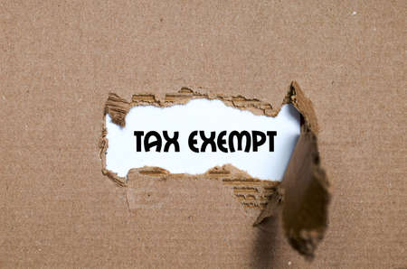exempt: The word tax exempt appearing behind torn paper