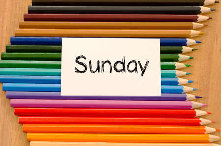 Sunday text on white paper and colored pencils on wooden background