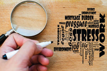 Stress word cloud design over wooden background and human hand