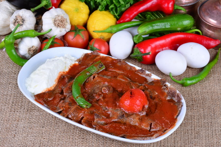Traditional Turkish Bursa Iskender kebab doner served with special sauce and yogurt red in the middle, garnished with grilled tomatoes and peppers Stock Photo