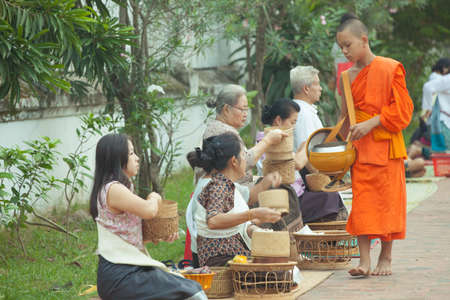 local festivals: People giving alms to buddhist monks on the street, Luang Prabang, 20 JUNE 2014