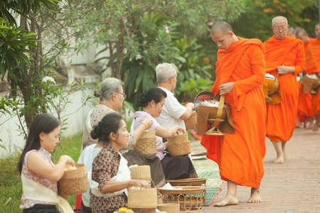 limosna: Las personas que dan limosna a los monjes budistas en la calle, Luang Prabang, 20 JUNE 2014