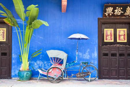 Старый рикша трехколесный велосипед рядом Fatt Цзы Mansion или голубой особняк