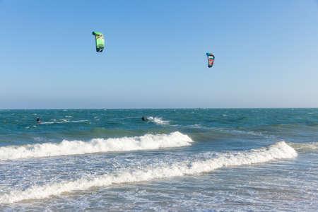kiter: Mui Ne, Vietnam - 24 March, 2014: Kiters ride on the waves at Mui Ne beach, Southern Vietnam on 24 March, 2014.