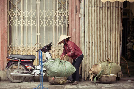 hard sell: Hanoi, Vietnam - 3 MARCH: Women with baskets on the street of Hanoi, March 3, 2014. Editorial