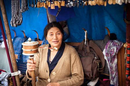 tibetian: Dharamsala, India - 28 September, 2014: Tibetian woman praying with traditional hand prayer wheel at the street market, Dharamsala, India.