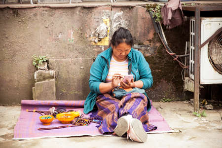 tibetian: Dharamsala, India - 28 September, 2014: Tibetian woman with a smartphone at the street market, Dharamsala, India. Editorial