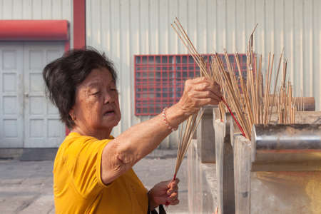 teng: Georgetown, Malaysia - 02 August, 2014: Old woman burns incense in Kuan Yin Temple, one of the oldest Chinese temples on Penang on 02 August 2014, Georgetown, Malaysia.