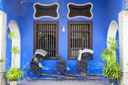 Georgetown, Malaysia � 04 August, 2014: Old rickshaw tricycle near Fatt Tze Mansion or Blue Mansion, famous oriental historical building in Georgetown, Penang, Malaysia on 04 August, 2014. Stock Photo - 38183953