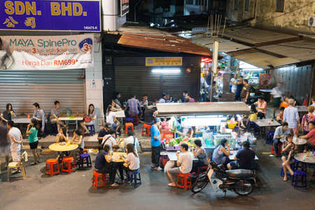 Georgetown, Malaysia - 03 August, 2014: The crowd of people dining at the street food stalls on Lebuh Chulia in historic part of Chinatown on 03 August 2014, Georgetown, Malaysia. Stock Photo - 38298387