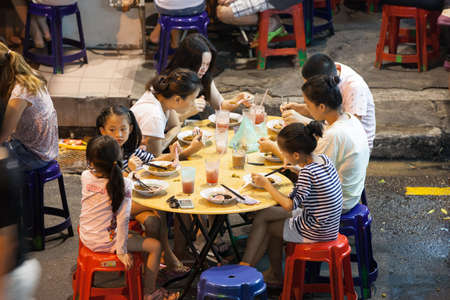 Georgetown, Malaysia - 03 August, 2014: Malaysian family dining at the street food stalls on Lebuh Chulia in historic part of Chinatown on 03 August 2014, Georgetown, Malaysia.