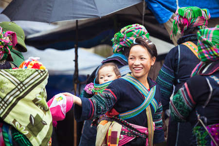 Sapa, Lao Cai, Vietnam - 6 May 2014: Hmong tribal woman with baby in national clothes on the local market, Sapa, Northern Vietnam on 06 May 2014.